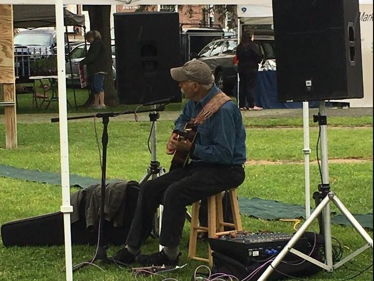 Photo of Tom Pirozzoli playing guitar at Lebanon Farmers' Market
