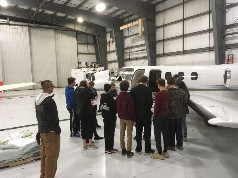 Photo of students looking at plane inside hanger