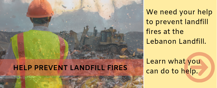 photo of worker in yellow vest looking out over landfill fire